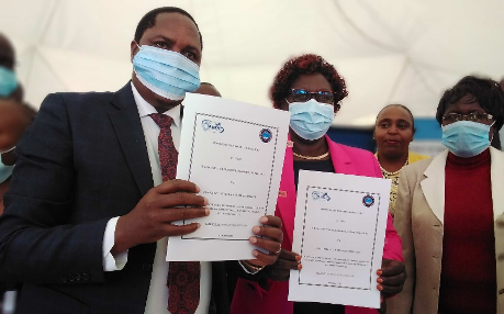 Signed MoU for Aquaculture Business Development Programme (ABDP) being displayed. From left is Sammy Macaria, ABDP National Coordinator, RIAT BOG Chair, Dr Lily Kisaka and RIAT Principal, Marren Omondi (far behind is Dr. Caroline Karugu, Nyeri Deputy Governor)